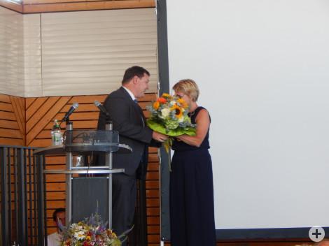 Bürgermeister Lehrer überreicht Rektorin Wiedmann einen Blumenstrauß.